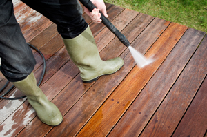 Person Pressure Washing a Wooden Deck Marietta GA