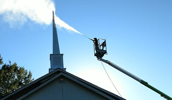 pressure washing worker cleaning chimney